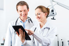 Team of doctors in clinic with tablet computer Stock Photography