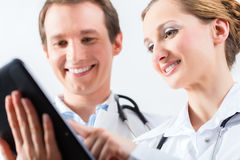 Team of doctors in clinic with tablet computer Stock Photo