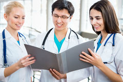 Team of doctors. Doctor giving his younger colleague a piece of advice concerning the diagnosis Stock Image