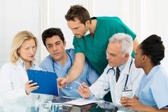 Team Of Doctors Examining Reports Arkivbilder