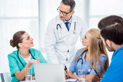 Team of doctors having conversation. Team of doctors and general practitioner having conversation and using laptop Stock Image