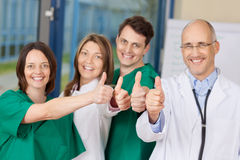 Team Of Doctors Gesturing Thumbs Up Sign. Portrait of confident team of doctors gesturing thumbs up sign in hospital Stock Images