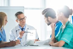 young team of doctors and general practitioner having conversation and looking stock images