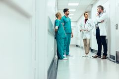 Team of doctors having discussion in hospital corridor. Group of medical staff discussing in clinic hallway. Healthcare professionals having discussion in royalty free stock images