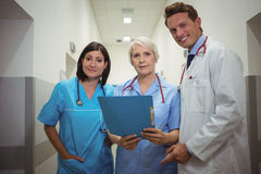Team of doctors having discussion over file in corridor Stock Photo