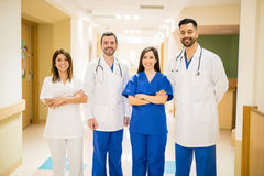 Team of doctors in a hospital hallway. Portrait of a team of Hispanic doctors standing in a hospital hallway and smiling royalty free stock images