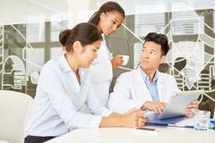 Team of doctors in meeting. Working with tablet in hospital Stock Photo