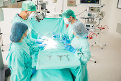 Team of doctors in the middle of surgery. Group of four young surgeons working together as a team while operating on a patient Stock Photo