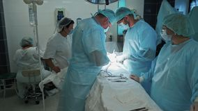 Team of doctors and nurses in sterile clothing during surgery. Slow motion. Team of doctors and nurses in sterile clothing during surgery, slow motion. Surgeon stock video