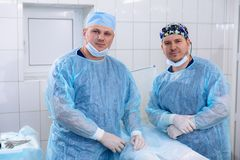 A team of doctors in the operating room conducts medical procedures. Surgeons in sterile clothing work in the hospital. Medical equipment in the clinic Royalty Free Stock Image