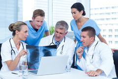 Team of doctors working on laptop and analyzing xray Stock Photos