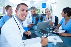 Team of doctors working on laptop and analyzing xray Stock Image