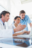 Team of doctors working on laptop computer Stock Images