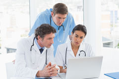 Team of doctors working on laptop computer Stock Photography