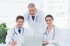 Team of doctors working together with their laptop looking at ca Stock Photos