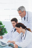 Team of doctors working together and watching something on their Stock Image