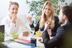 Team eating business lunch. Horizontal view of team eating business lunch stock photo