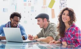Team of editors at work with one smiling at camera. In modern creative office Stock Photo