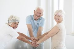 Team of elders. Team of happy elders with joined hands before fitness classes Stock Photo