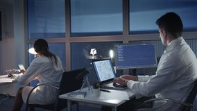 Team of electronics engineers in white coats working on the computers in advanced laboratory. Smart people working together. Back view stock footage