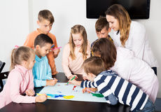 Team of elementary age children drawing. Portrait beautiful team of elementary age children and teacher drawing on one sheet Stock Photos