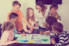Team of elementary age children drawing. Portrait happy team of elementary age children and teacher drawing on one sheet Royalty Free Stock Image