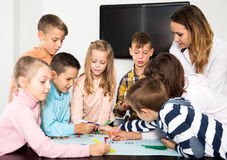 Team of elementary age children drawing. Positive team of elementary age children and female teacher drawing on one sheet Royalty Free Stock Photos