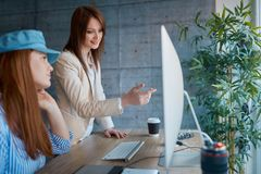 Team of employees is discussing the project working in the office with computers. stock image
