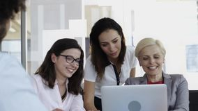 Team of employees working on computer together in their office stock footage