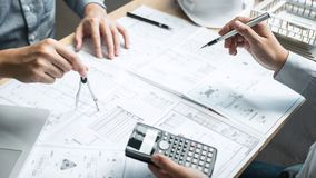 Team of engineering or architect meeting and discussing on blueprint and building model while checking information on sketching royalty free stock photo