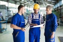 Team Of Engineers Having Discussion i fabrik arkivbilder