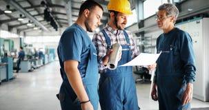Team Of Engineers Having Discussion i fabrik arkivfoton