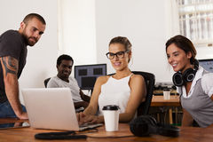 Team of entrepreneurs in a startup office. Team of young entrepreneurs looking at a laptop computer in a tech startup office Stock Image