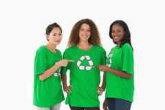 Team of environmental activists smiling at camera pointing to tshirt Royalty Free Stock Photos