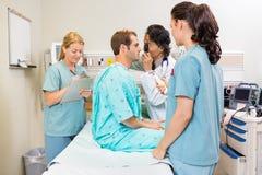 Team Examining Patient In Hospital medico Fotografia Stock Libera da Diritti