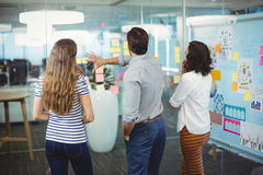 Team of executives discussing over sticky notes in office royalty free stock images