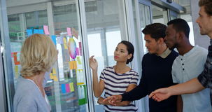 Team of executives discussing over sticky notes
