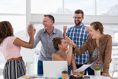 Team of executives giving high five to each other. In the office royalty free stock photos