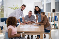 Team of executives interacting with each other while working in the office. Smiling team of executives interacting with each other while working in the office Stock Photography