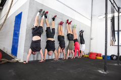 Team exercising handstands at fitness gym center Stock Images