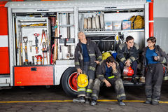 Team Of Exhausted Firefighters At Station. Team of exhausted male and female firefighters at truck in fire station Stock Image