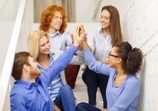 Team facendo il gesto di livello cinque che si siede sulla scala Immagine Stock Libera da Diritti