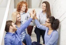 Team facendo il gesto di livello cinque che si siede sulla scala Immagine Stock
