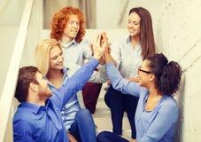 Team facendo il gesto di livello cinque che si siede sulla scala Fotografia Stock