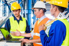 Team in Factory at production training. Team of workers and engineer  in Factory at production training with laptop Royalty Free Stock Image