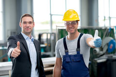Team in factory with thumbs up Stock Photos