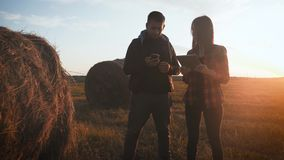 Team farmers stand in field holding tablet on the farm and use technology to predict the future agriculture growth stock footage