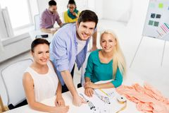 Team of fashion designers working at office. Fashion design, tailoring and people concept - team of designers with sketch working at office royalty free stock photo