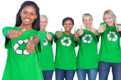 Team of female environmental activists smiling at camera and giv Royalty Free Stock Images