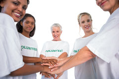 Team of female volunteers with hands together smiling at camera Stock Photo